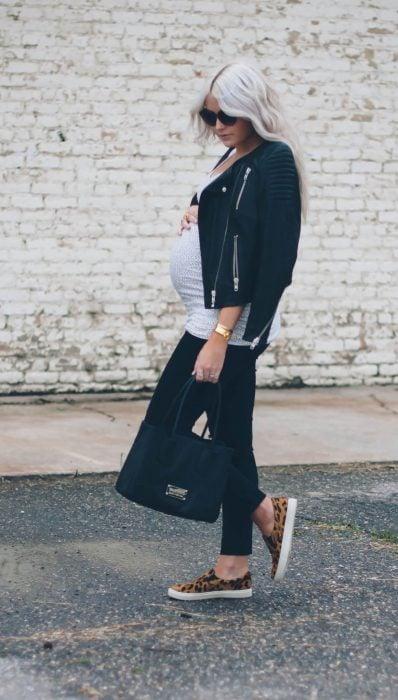 Chica embarazada usando unos leggins de color negro, blusa gris y chamarra de cuero