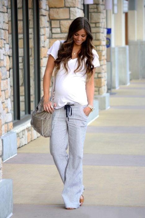 Chica embarazada usando un pantalón gris y blusa blanca