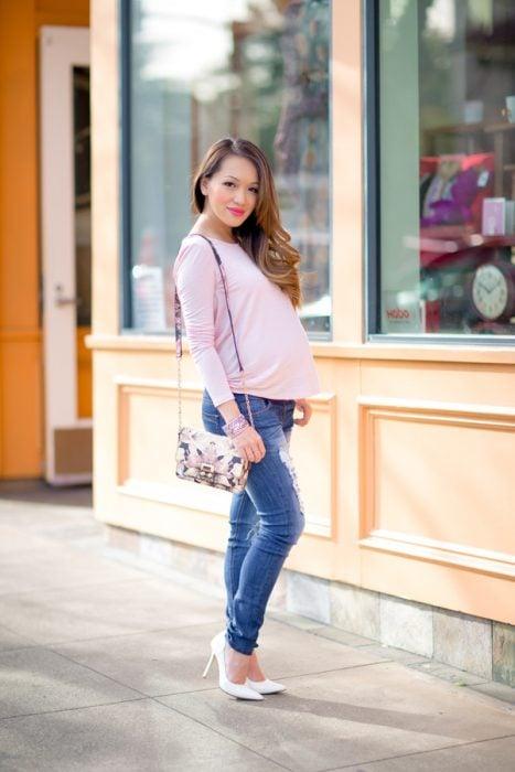 Chica embarazada usando una blusa rosa y pantalón de mezclilla