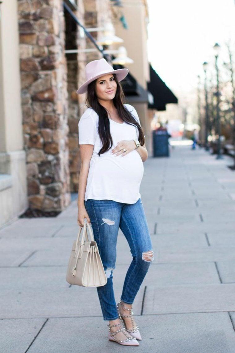 Chica embarazada con sombrero, blusa blanca, pantalón de mezclilla y  zapatos color café