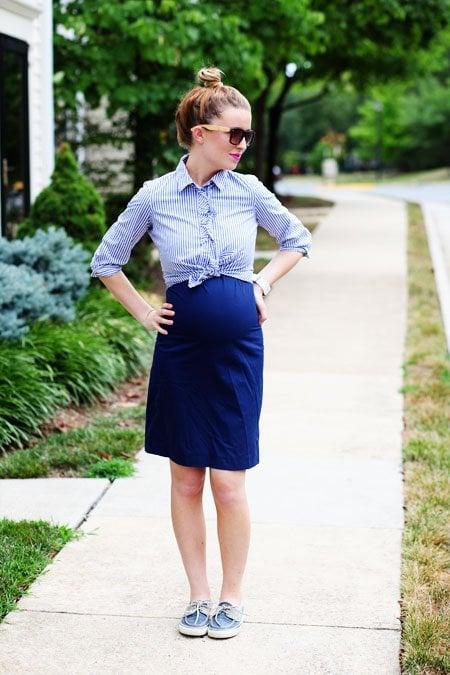 Chica embarazada con una falda en color azul y blusa en color blanco con líneas