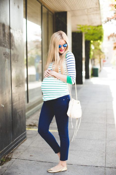 Chica embarazada usando una blusa color verde y pantalón de mezclilla