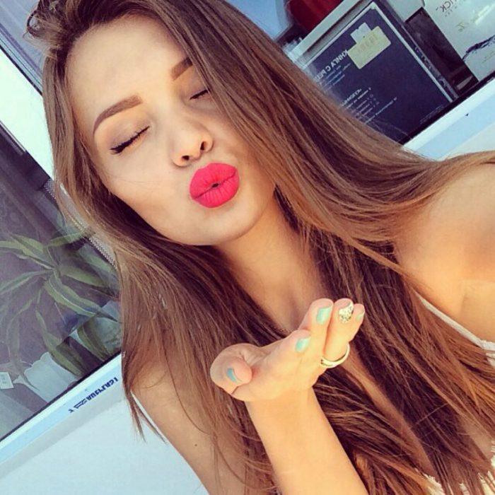 mujer de cabello largo y castaño enviando beso