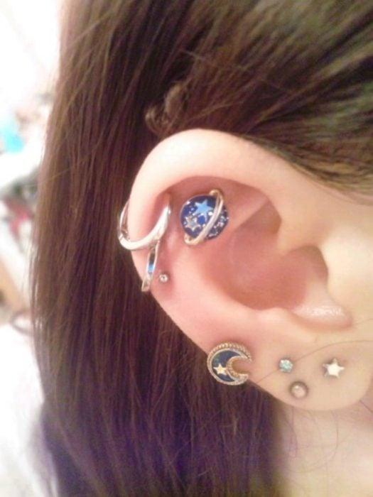 Chica con un piercing en la oreja en forma de planetas y lunas