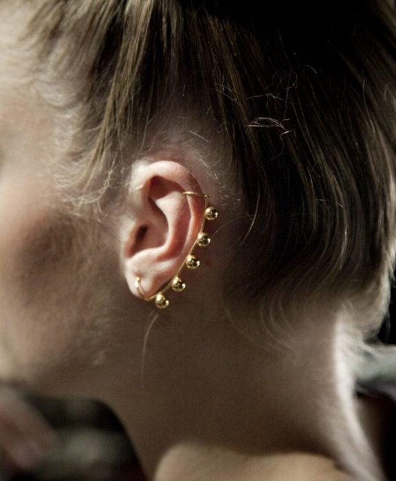 Chica con un piercing en la oreja con varias perlas doradas