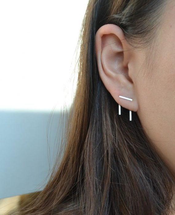 Chica con un piercing en la oreja en forma de grapa