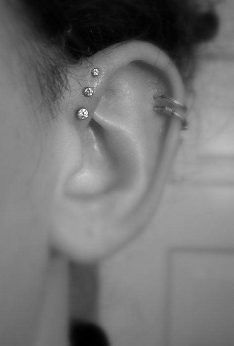 Chica con un piercing en la oreja con tres broqueles