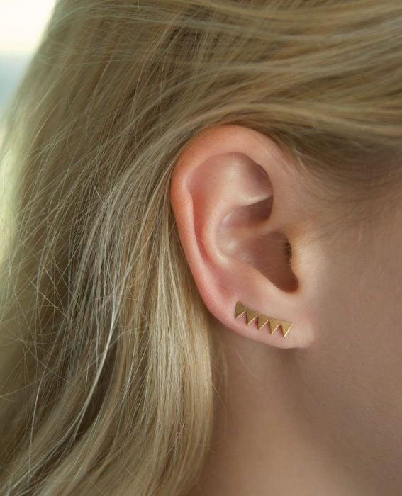 Chica con un piercing en la oreja con forma de flechas