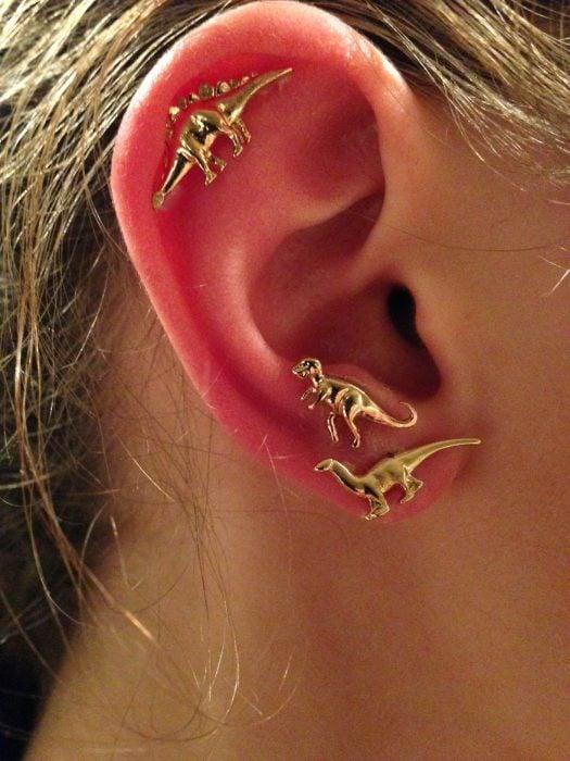 Chica con un piercing en la oreja en forma de dinosaurios