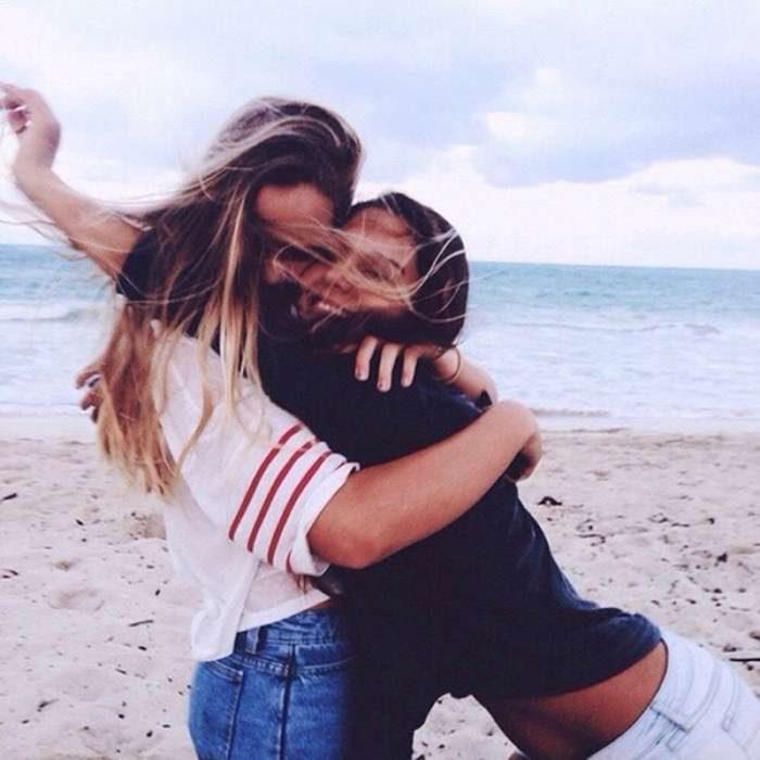 mujer rubia abrazando a otra chica en la playa