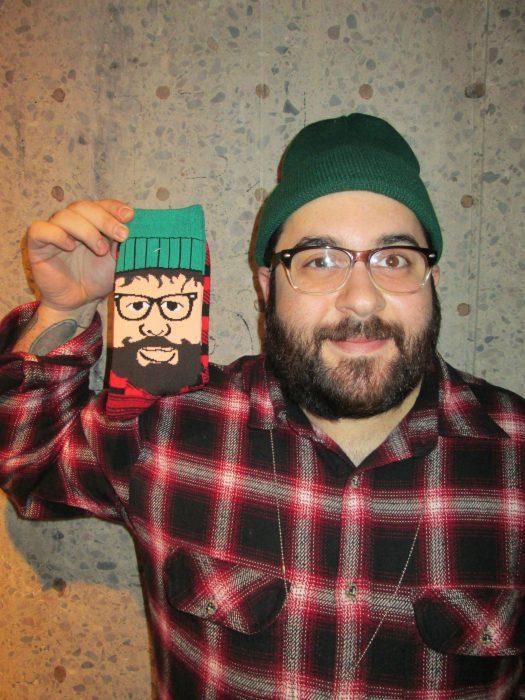 hombre con barba lentes, gorra verde y camisa de leñador sosteniendo celular