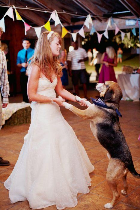 mujer rubia con vestido de novia bailando con perro