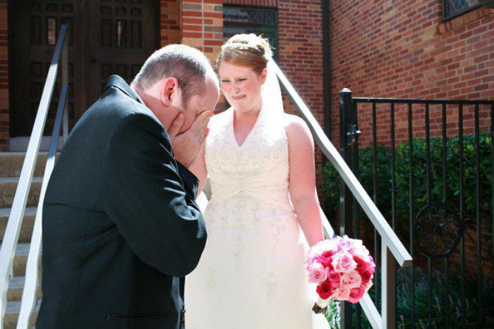 Novio llorando al ver a su novia parada en unas escaleras