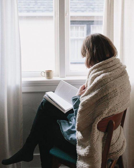 Chica leyendo frente a la ventana con una taza de café