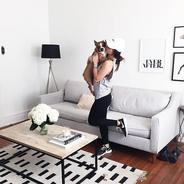 Chica abrazando a un perro mientras está en la sala de su casa