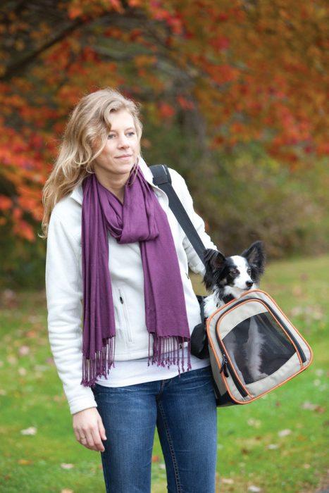 Chica llevando a su perro en una canastilla transportadora