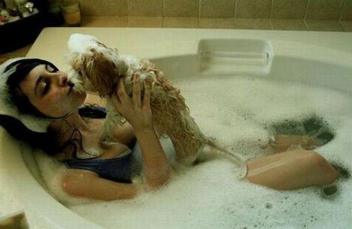 Chica tomando un baño de espuma junto a su perro