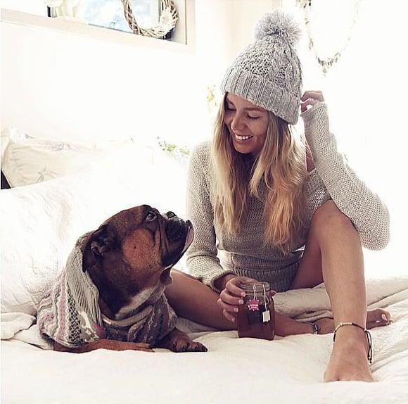 Chica sentada junto a su perro bebiendo té
