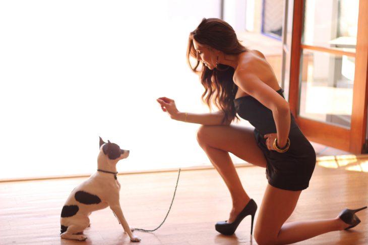 Chica sentada frente a un perro jugando con él