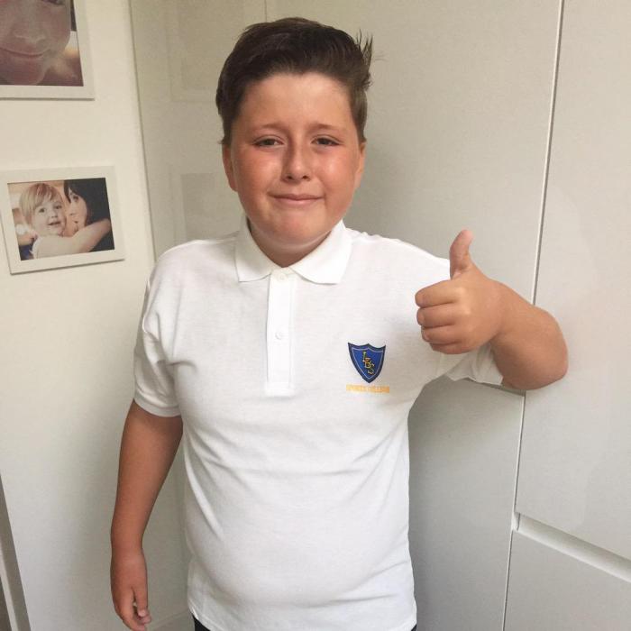 niño rubio con camisa blanca sonrie