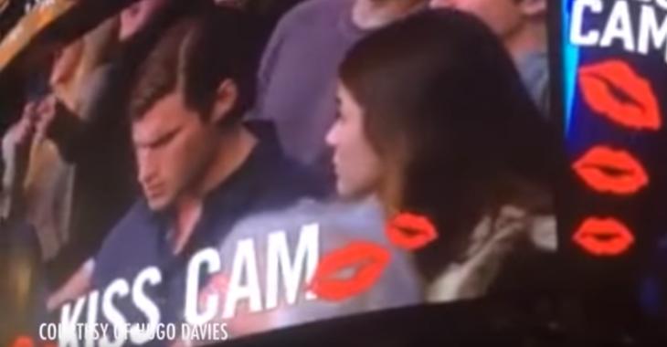 Hombre en celular y mujer lo ve triste cámara del beso