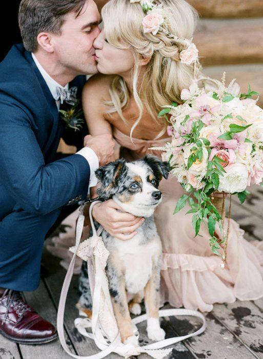 pareja de recien casados besándose y abrazando a perro
