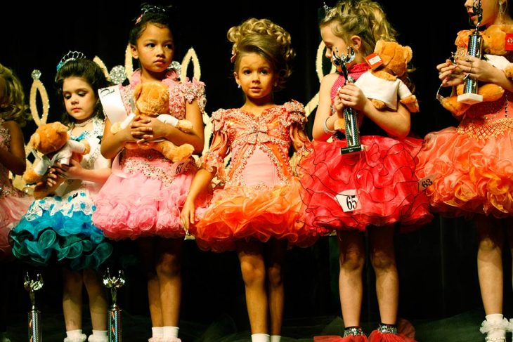 gurpo de niñas con cabello rubio, tiaras y vestidos