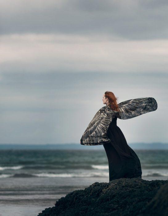 Chica parada sobre una roca contemplando el mar mientras tiene los brazos extendidos