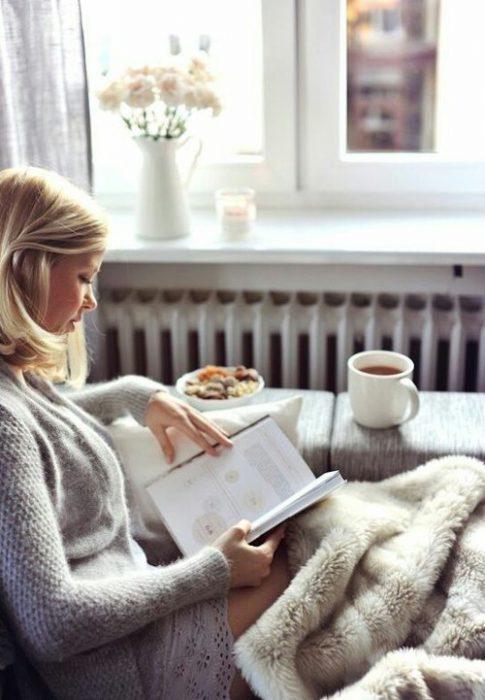 Chica sentada en un sofá leyendo un libro y bebiendo café