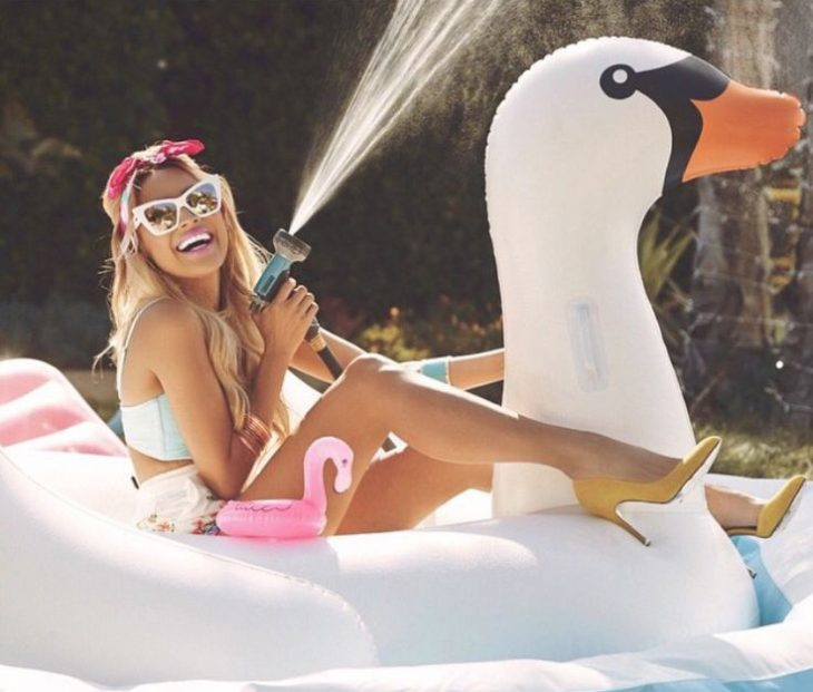 Chica sentada sobre un cisne inflable mientras tira agua con una manguera