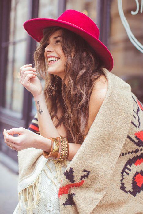 Chica usando un poncho y un sombrero rojo mientras está sentada en unas escaleras