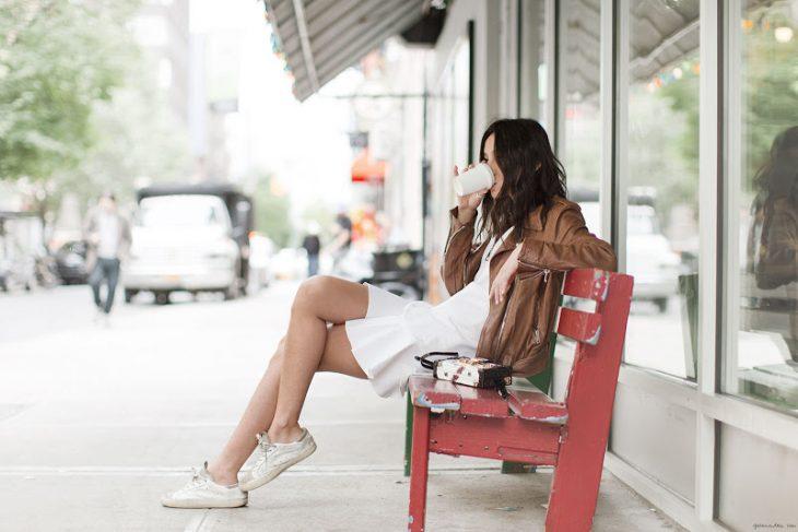Chica sentada en una banca bebiendo café