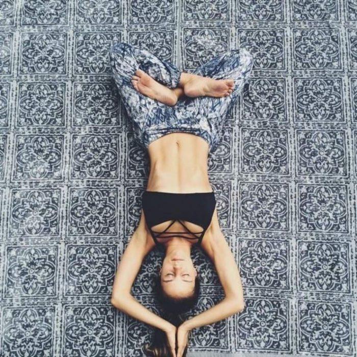 Chica haciendo posiciones de yoga mientras está recostada en un tapete