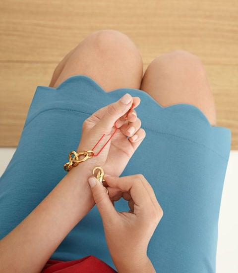 Chica poniendose una pulsera con ayuda de un clip
