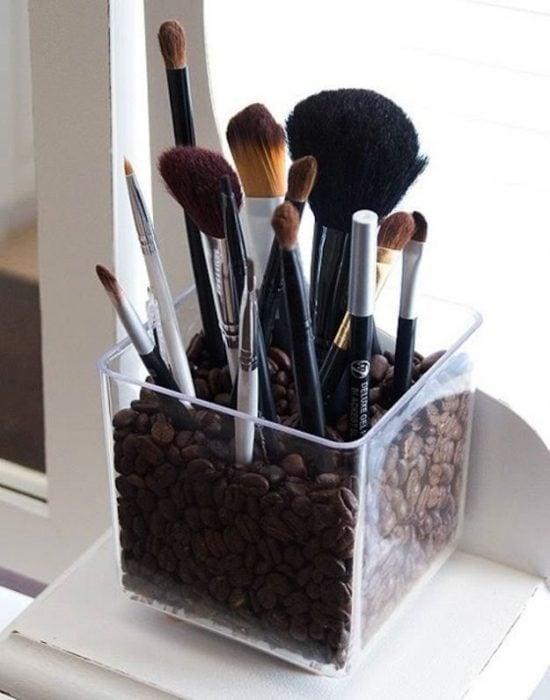 Brochas de maquillaje colocadas en un recipiente con granos de café