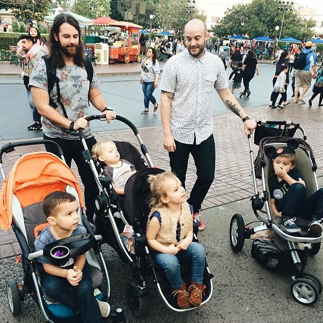 papás guapos DILFs con bebé en Disneyland