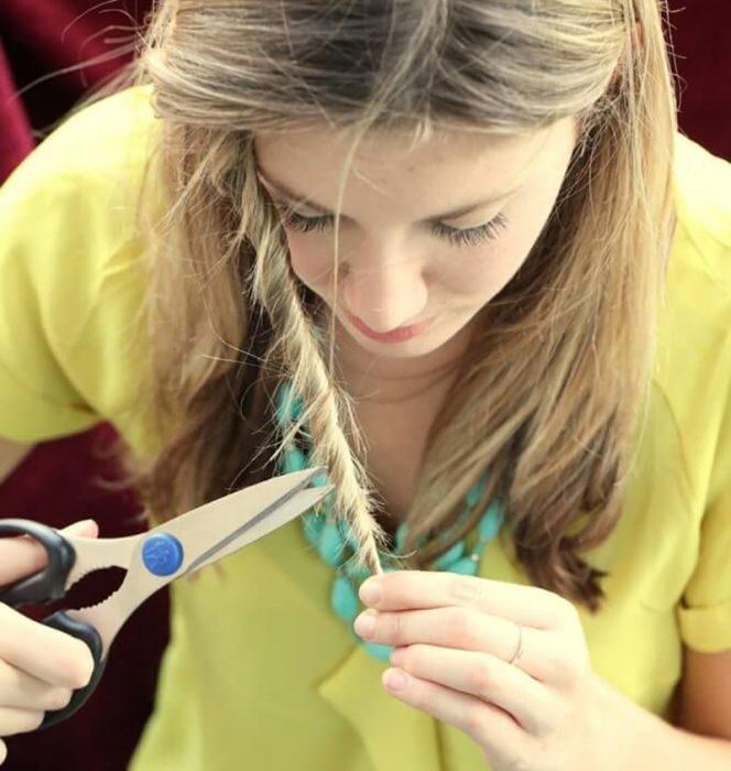 mujer rubia enrollandose el cabello y recortando sus puntas