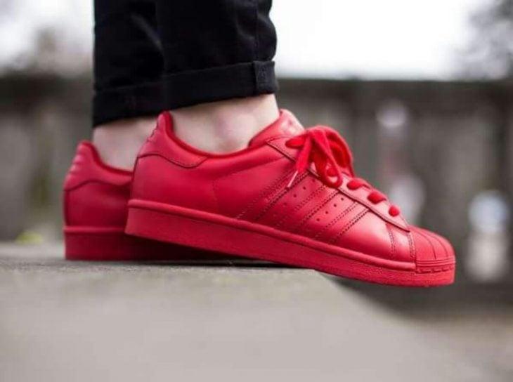 pies de mujer con tenis adidas superstar rojo