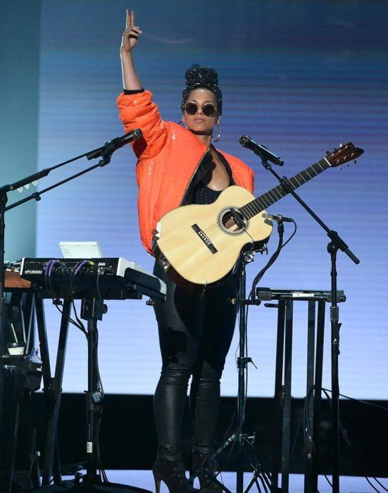 mujer de chamarra naranja con guitarra en escenario