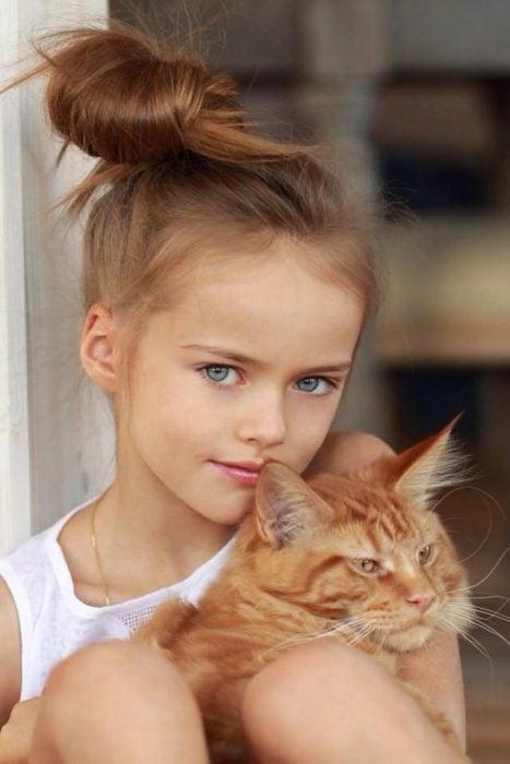Kristina Pimenova cuando era pequeña, abrazando a su gato.