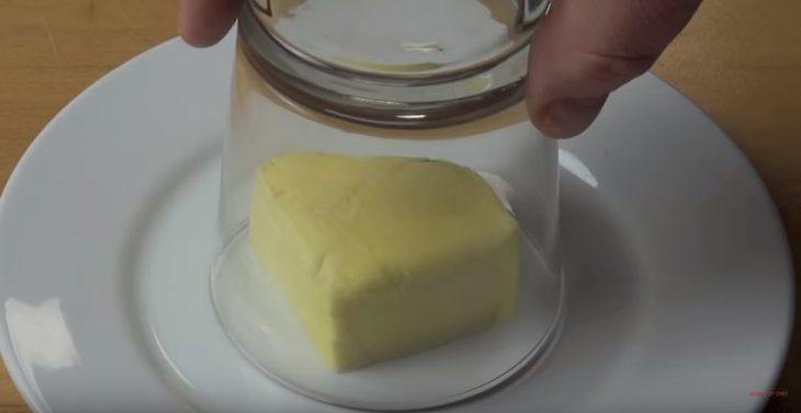 Mantequilla bajo un vaso de vidrio.