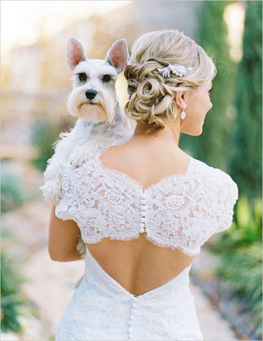 mujer novia con vestido blanco cargando perro