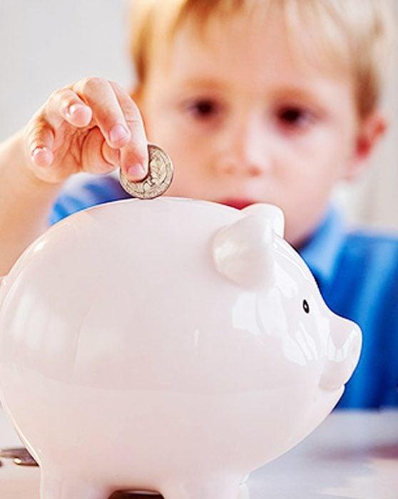 Niño metiendo una moneda en el cochinito.