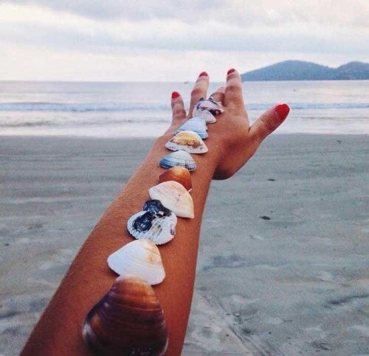 Mano con conchitas apuntando a la playa