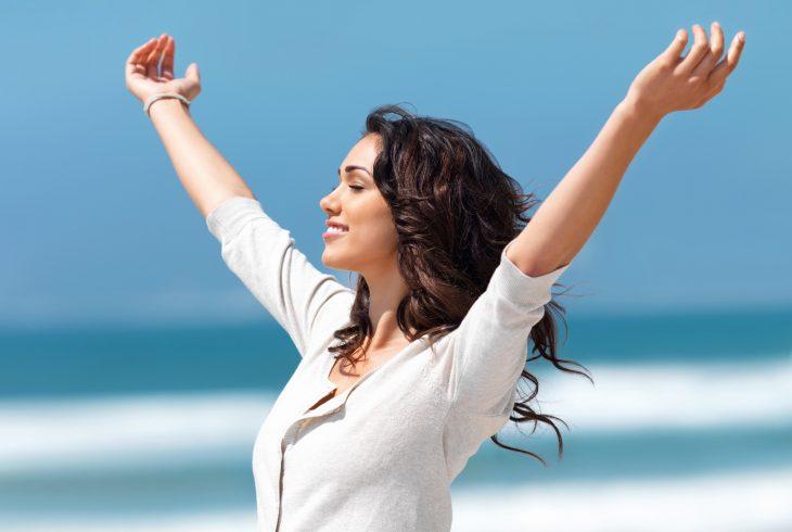 Mujer en la playa con sus brazos abiertos apuntando al cielo