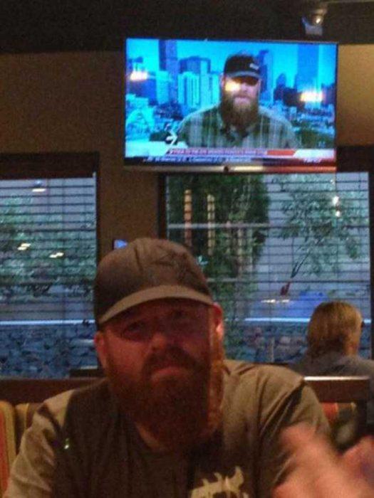 hombre con barba y gorra sentado en un bar y televisión atrás