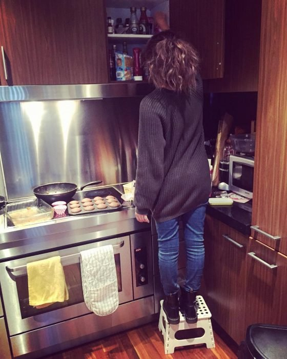 chica bajita sobre banco en cocina