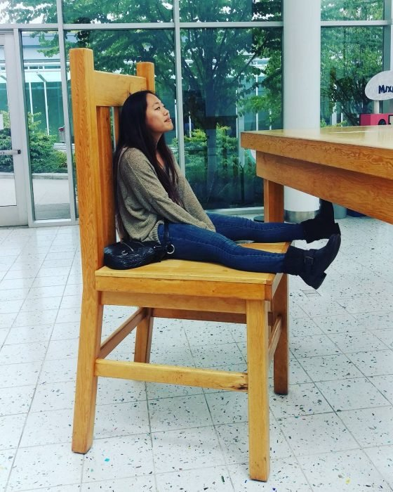 chica bajita sentada en silla grande