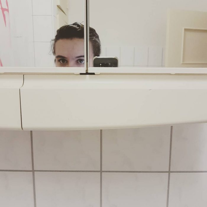 chica bajita tomando selfie en el baño