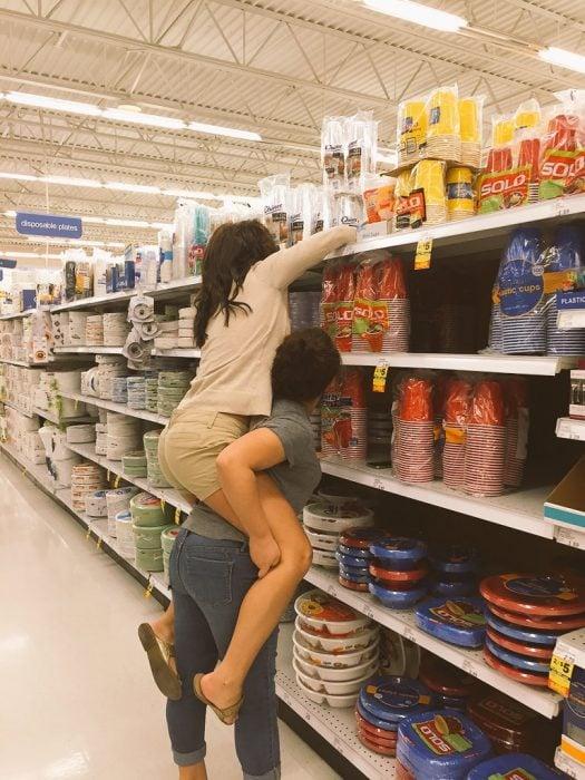 chica cargando a otra para alcanzar comida